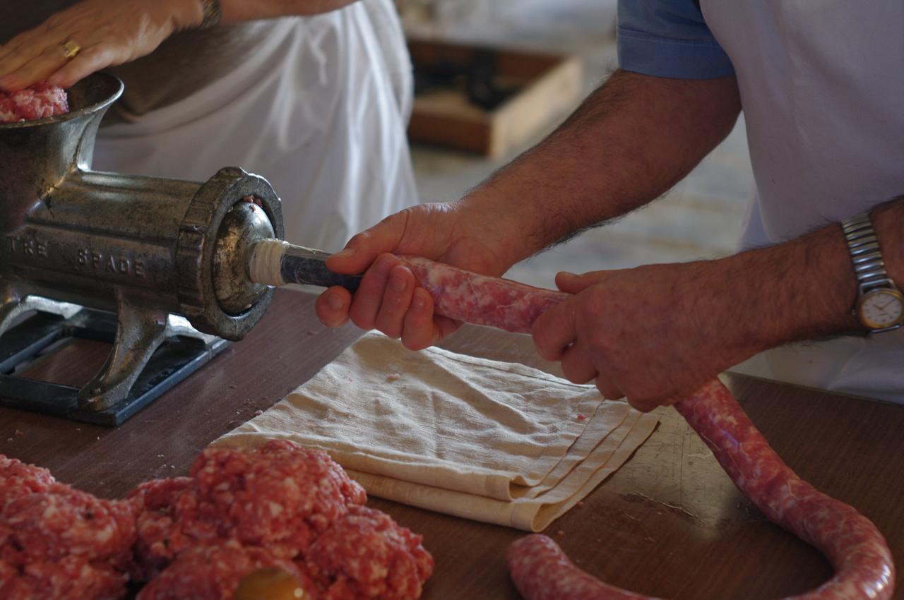 Il salamino inizia a formarsi: il norcino, con le mani bagnate d'acqua calda, fa scorrere con sapienza l'insaccato, mantenendo costante la velocità ed il diametro del prodotto finito.